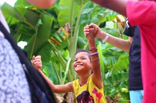 村に着いたばかりのメンバーの手を取り、すぐに遊びはじめる子どもたち。