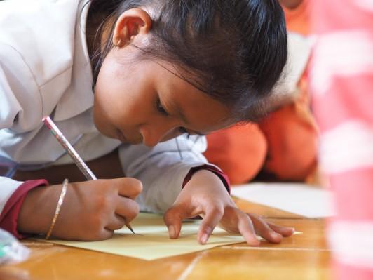 私たちが届けた日本製の鉛筆とノートで真剣に絵を書く女の子。
