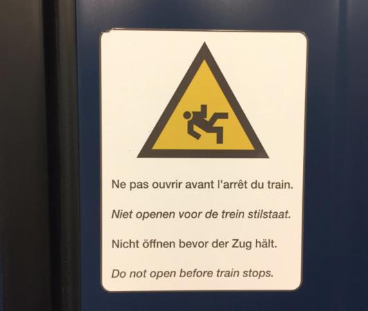 上からフランス語、オランダ語、ドイツ語、英語で「電車が停車するまでドアを開けないでください。」多言語国家ならではの電車の注意書き。